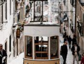 brown tram along buildings