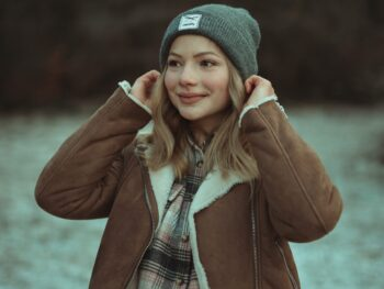 woman in brown coat and gray knit cap